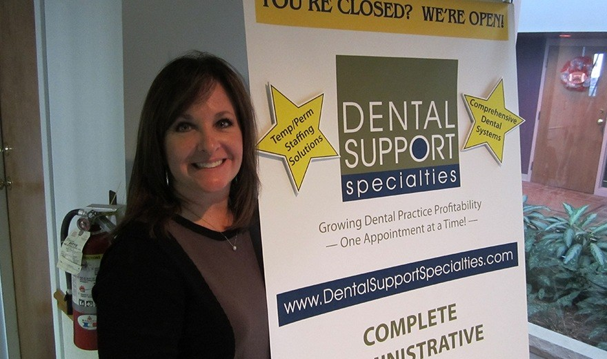 Mary Beth with Dental Support Specialties sign at event