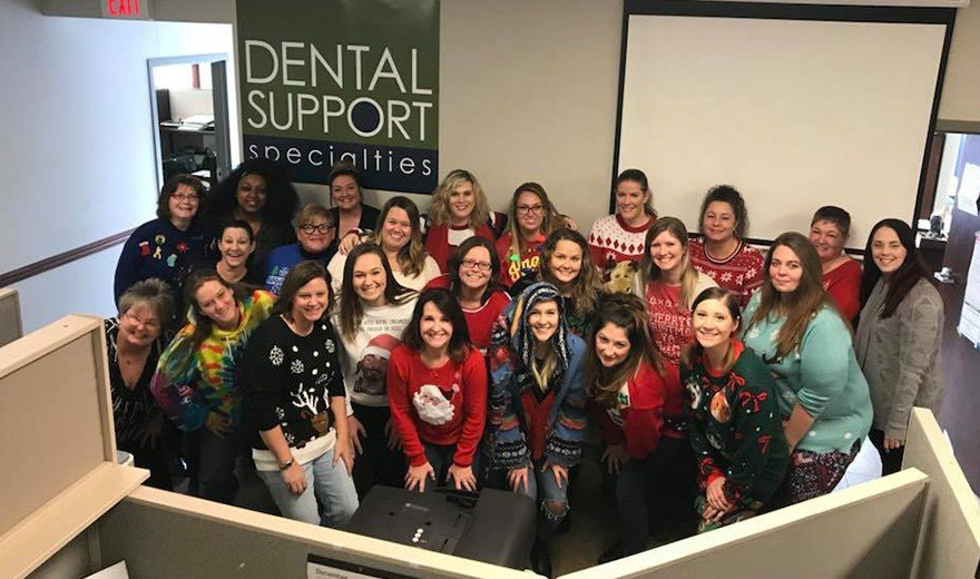 Team members wearing Christmas sweaters