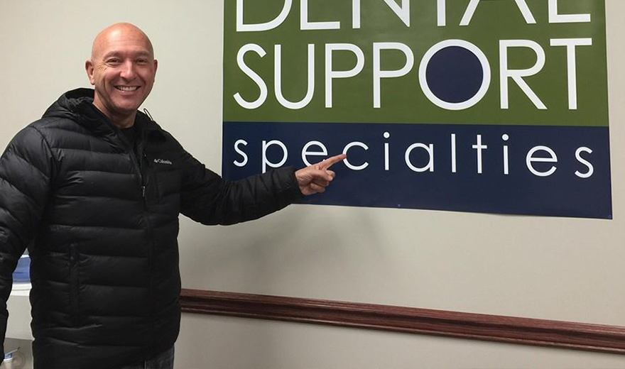 Team member pointing to Dental Support Specialties sign