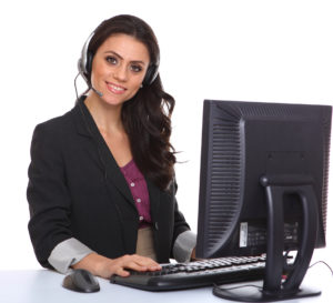 Smiling woman with computer and phone headset