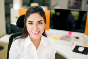 Young smiling woman at work station