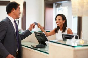 A receptionist handing a patient their credit card.