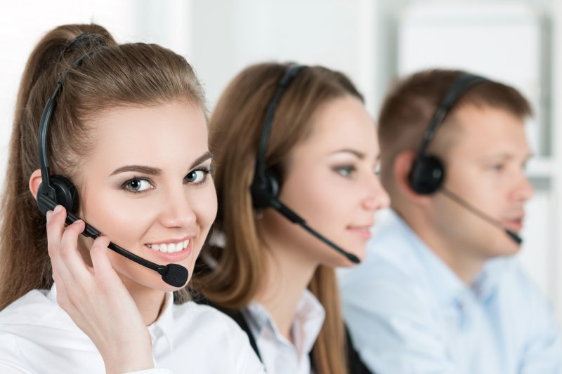 A woman smiling with a group of call center employees.