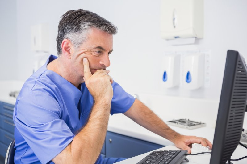 A dentist staring at a monitor.