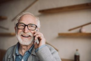 man smiling talking on phone, dental scheduling