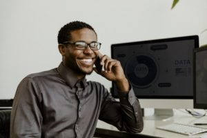man smiling and talking with dental answering service