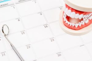 teeth and dental tool on calendar for patient scheduling