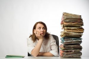 woman looking at a stack and needing dental insurance support
