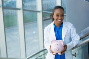 dentist holding a piggy bank getting help with dental insurance verification